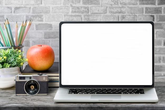 Maquete do computador portátil com suprimentos na mesa de madeira Foto Premium