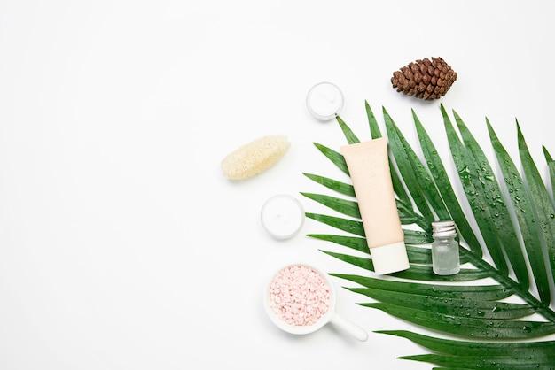 Maquete do frasco de creme cosmético, pacote de rótulo em branco e ingredientes em um fundo de folhas verdes. Foto Premium