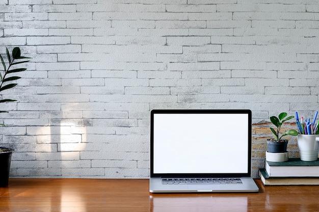 Maquete laptop com tela em branco, planta de casa e pilha de livro na mesa de madeira, tela em branco para design gráfico. Foto Premium