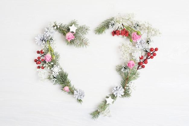 Maquete natal coração grinalda com abeto, hypsophila, cones e flocos de neve em estilo rústico, com lugar para o seu texto Foto Premium