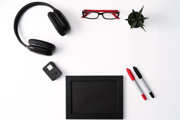 Maquete, photo frame, câmera de ação, fones de ouvido, óculos, caneta e cacto, objeto vermelho e preto sobre fundo branco Foto Premium
