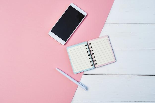 Maquete plana leiga composição com smartphone e o bloco de notas em um fundo azul e rosa. área de trabalho com espaço de cópia Foto Premium