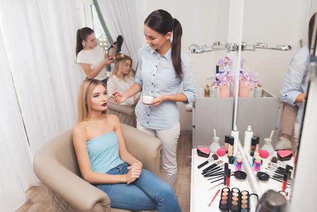 Maquiador aplica o blush para a garota com pincéis. Foto Premium