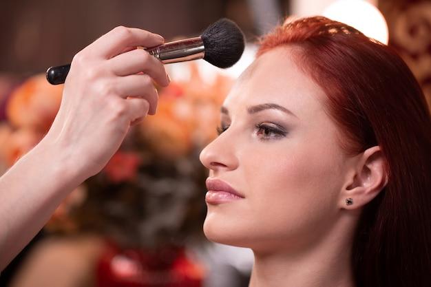 Maquiador aplicando base líquida tonal no rosto da mulher de branco compõem o quarto. Foto Premium
