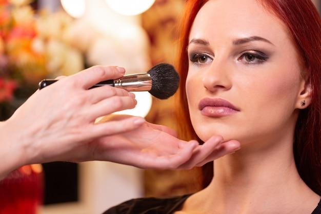 Maquiador aplicando base tonal líquida no rosto da mulher Foto Premium