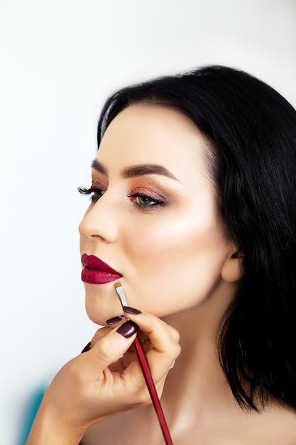 Maquiador aplicando sombra para uma mulher Foto Premium