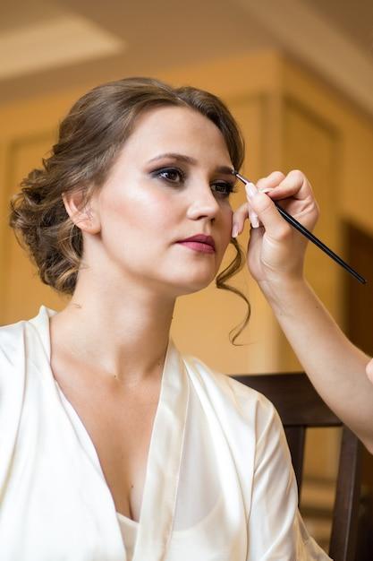 Maquiador de casamento fazendo uma maquiagem para noiva. manhã nupcial de uma senhora bonita. acusações da noiva Foto Premium