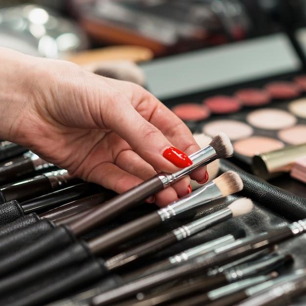 Maquiador feminino com coleção de pincéis profissionais Foto gratuita