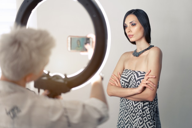Maquiador fotografa no celular resultado de seu trabalho Foto Premium