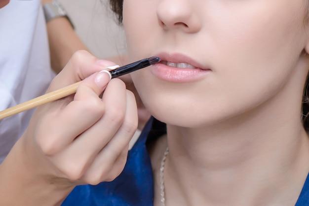 Maquiador pinta os lábios da menina com um pincel Foto Premium