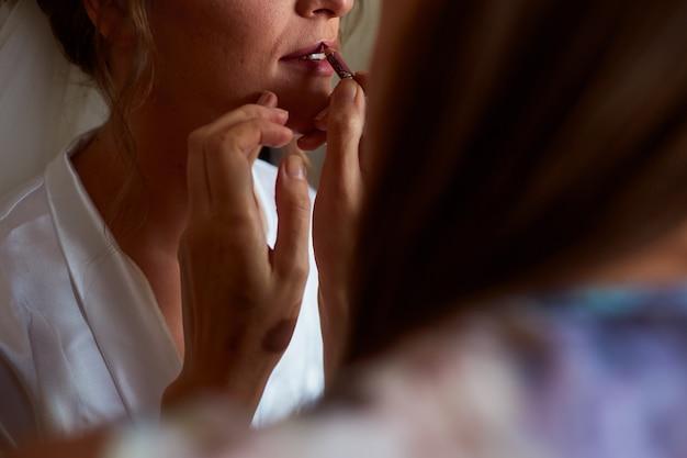 Maquiador pinta os lábios da noiva com um batom vermelho Foto gratuita