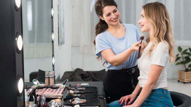 Maquiador, pulverizando o rosto da loira Foto gratuita
