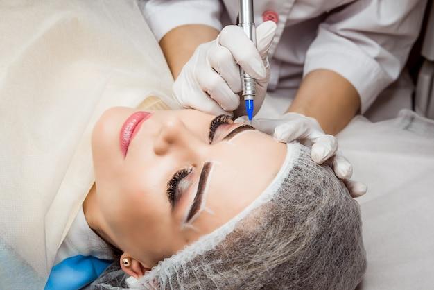Maquiagem permanente para sobrancelhas. closeup de mulher bonita com sobrancelhas grossas no salão de beleza. esteticista fazendo sobrancelha tatuagem para o rosto feminino. procedimento de beleza. Foto Premium