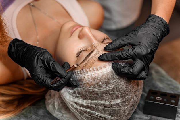 Maquiagem permanente sobrancelha no salão de beleza, closeup. esteticista profissional marca o comprimento das sobrancelhas com lápis e uma régua especial de medição de sobrancelha. tratamento de cosmetologia. Foto Premium