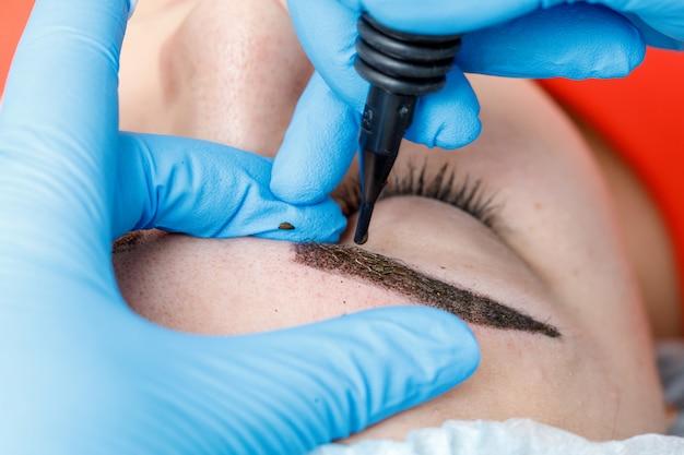 Maquiagem permanente, tatuagem de sobrancelhas. cosmetologista aplicar maquiagem Foto Premium