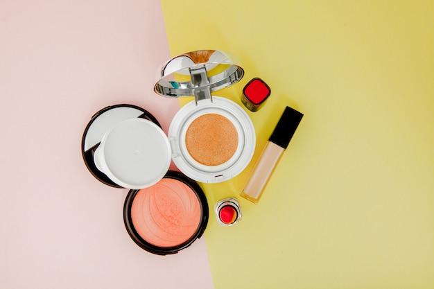 Maquiagem produtos derramando sobre um fundo amarelo e rosa brilhante com espaço de cópia Foto Premium