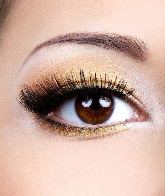 Maquilhagem de olhos da moda com sombra dourada - foto macro Foto gratuita