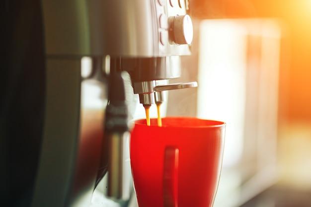 Máquina de café de close-up fazendo café fresco pela manhã, máquina de café e caneca vermelha Foto Premium