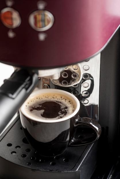 Máquina de café expresso close-up com uma xícara Foto gratuita