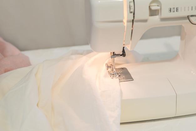 Máquina de costura, costura de tecido branco, alfaiate Foto Premium
