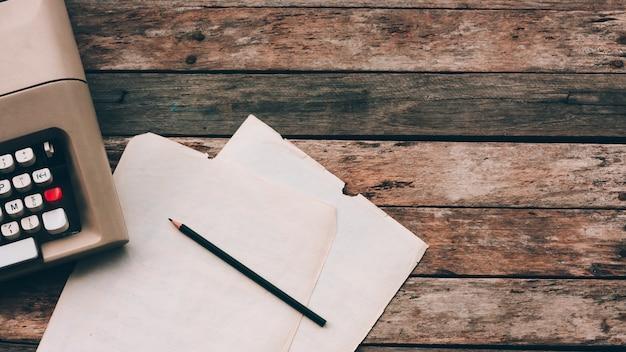 Máquina de escrever, lápis e papel com fundo de madeira. literatura, oficina de escrita criativa e jornalismo. Foto Premium