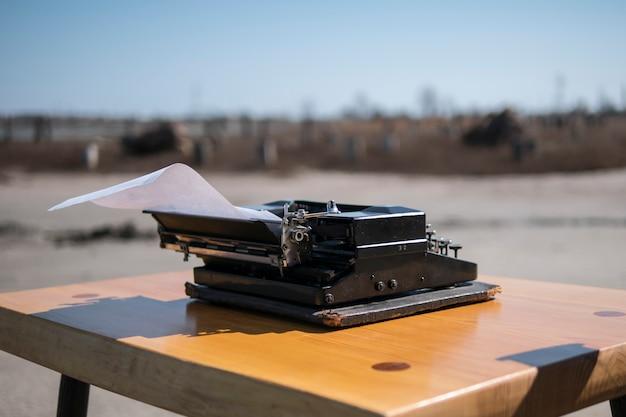 Máquina de escrever na mesa ao ar livre, estuário no fundo Foto Premium