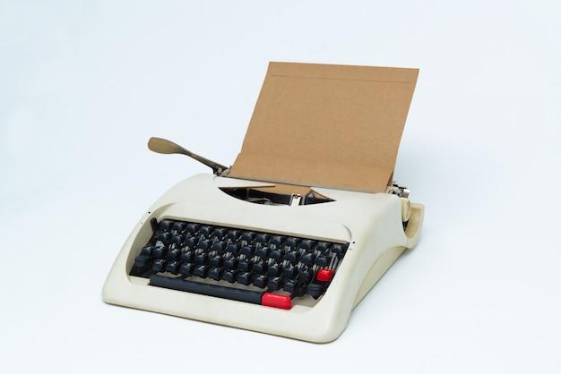Máquina de escrever retro com a folha do papel em branco no branco. Foto Premium