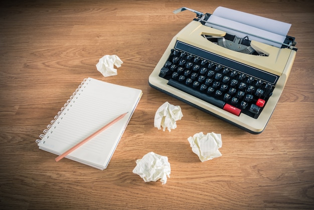 Máquina de escrever vintage e um caderno em branco de papel Foto Premium