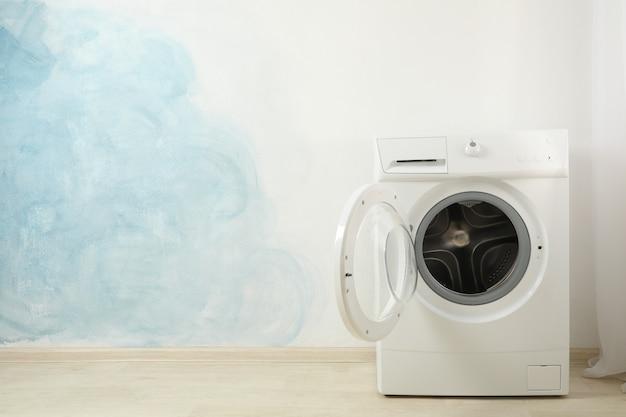 Máquina de lavar roupa moderna contra a parede azul, espaço para texto Foto Premium