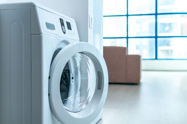 Máquina de lavar roupa moderna no quarto no apartamento. lavando roupa em casa. Foto Premium