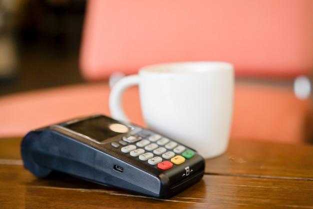 Máquina de pagamento com cartão de crédito com copo de café branco na mesa no café Foto Premium