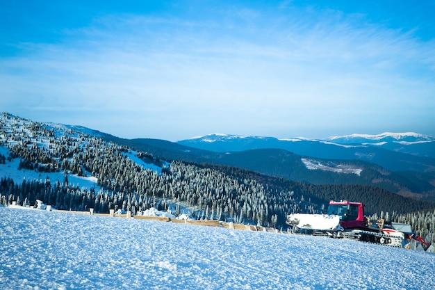 Máquina sopradora de neve trabalhando em uma estação de esqui com floresta e montanhas ao fundo em um dia ensolarado de inverno com céu azul Foto Premium