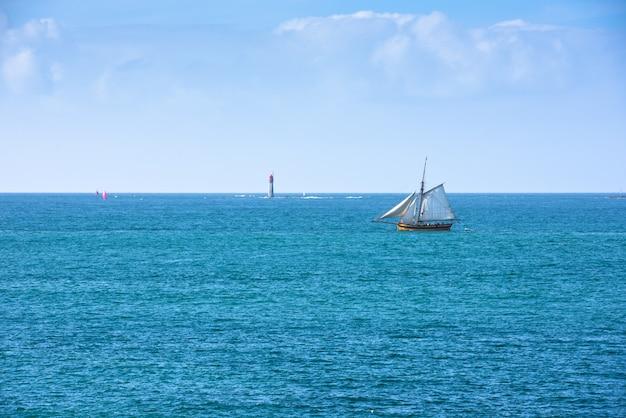 Mar azul brilhante e um iate no oceano Foto Premium