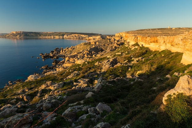 Mar cercado por rochas sob a luz do sol e um céu azul na costa noroeste, malta Foto gratuita