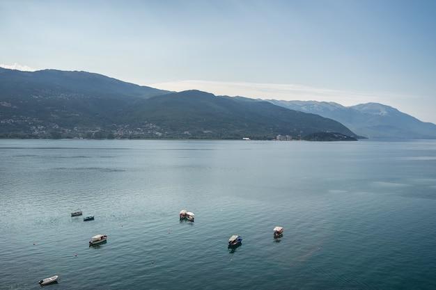 Mar com barcos rodeados por colinas cobertas de vegetação sob a luz do sol Foto gratuita