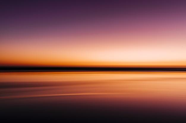Mar durante um pôr do sol colorido com uma longa exposição Foto gratuita