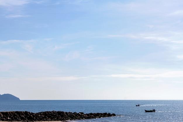 Mar e praia com barco de pesca na manhã de verão Foto Premium