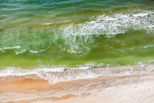 Mar, ondas e surf na costa arenosa em dias claros. vista aérea Foto Premium
