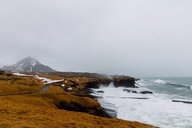 Mar ondulado cercado por rochas cobertas de neve e grama sob um céu nublado na islândia Foto gratuita