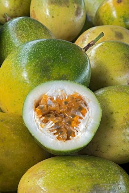 Maracujá azedo fatiado, pilha de frutas inteiras Foto Premium