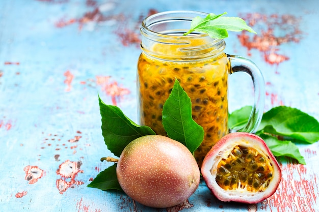 Maracujá em uma jarra de vidro com toda e meia fruta na mesa de madeira azul Foto Premium