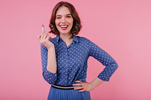 Maravilhosa mulher morena de camisa azul, posando com batom novo. menina caucasiana confiante com penteado elegante em pé na parede rosa. Foto gratuita