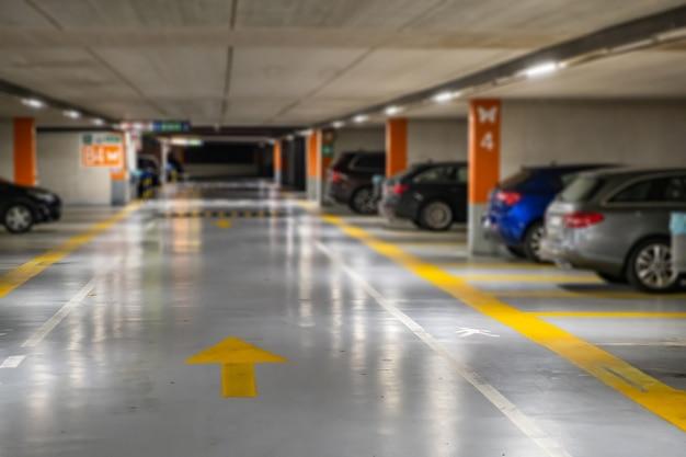 Marcações amarelas com carros modernos borrados estacionados dentro do estacionamento subterrâneo fechado. Foto Premium