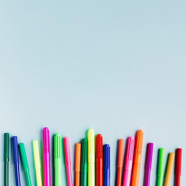 Marcadores multicoloridos na mesa azul Foto gratuita