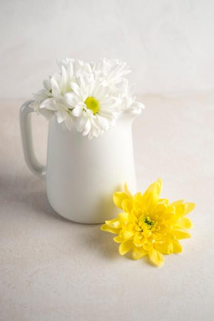 Margarida flores em jarro branco na mesa Foto gratuita