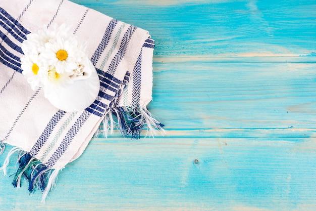 Margarida flores no jarro na mesa azul Foto gratuita