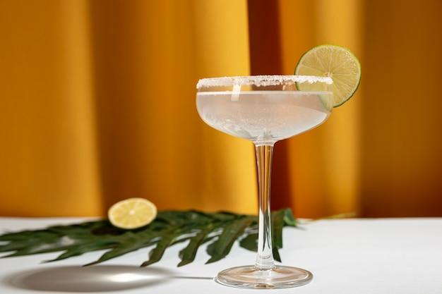 Margarita caseiro bebida com limão e folha de palmeira na mesa contra a cortina amarela Foto gratuita