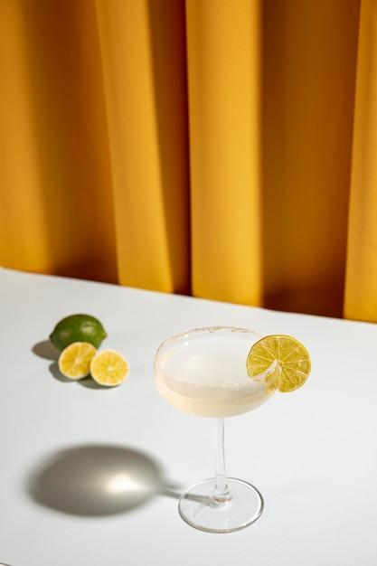 Margarita em vidro com limão na mesa branca contra a cortina amarela Foto gratuita