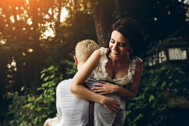 Marido carregar sua esposa no por do sol Foto gratuita