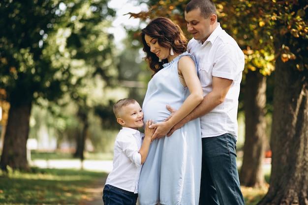 Marido com a esposa grávida e seu filho no parque Foto gratuita